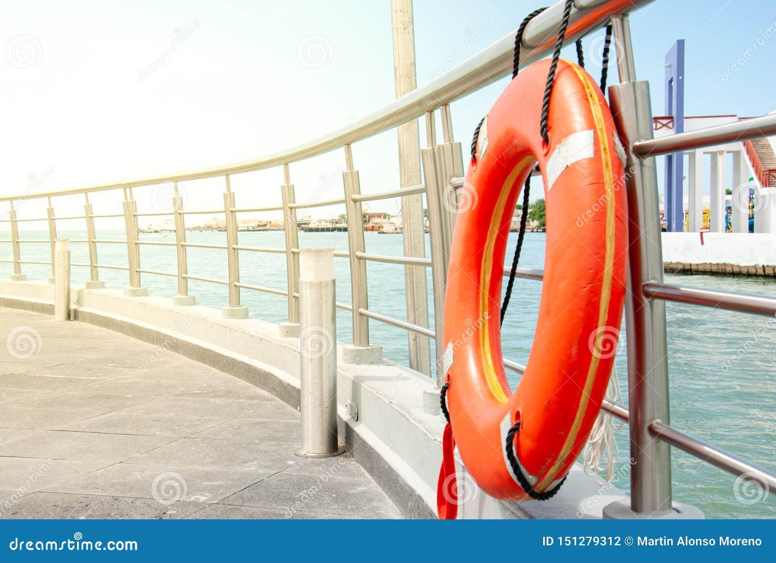 Pomarańczowy lifebuoy cumujący przy poręczem dok