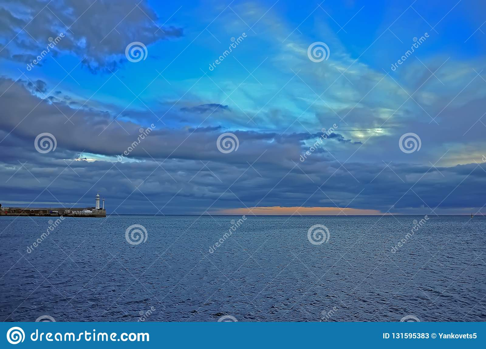 Pomarańczowy zmierzch wśród błękitnego jesieni nieba nad morzem blisko latarni morskiej przy Crimea