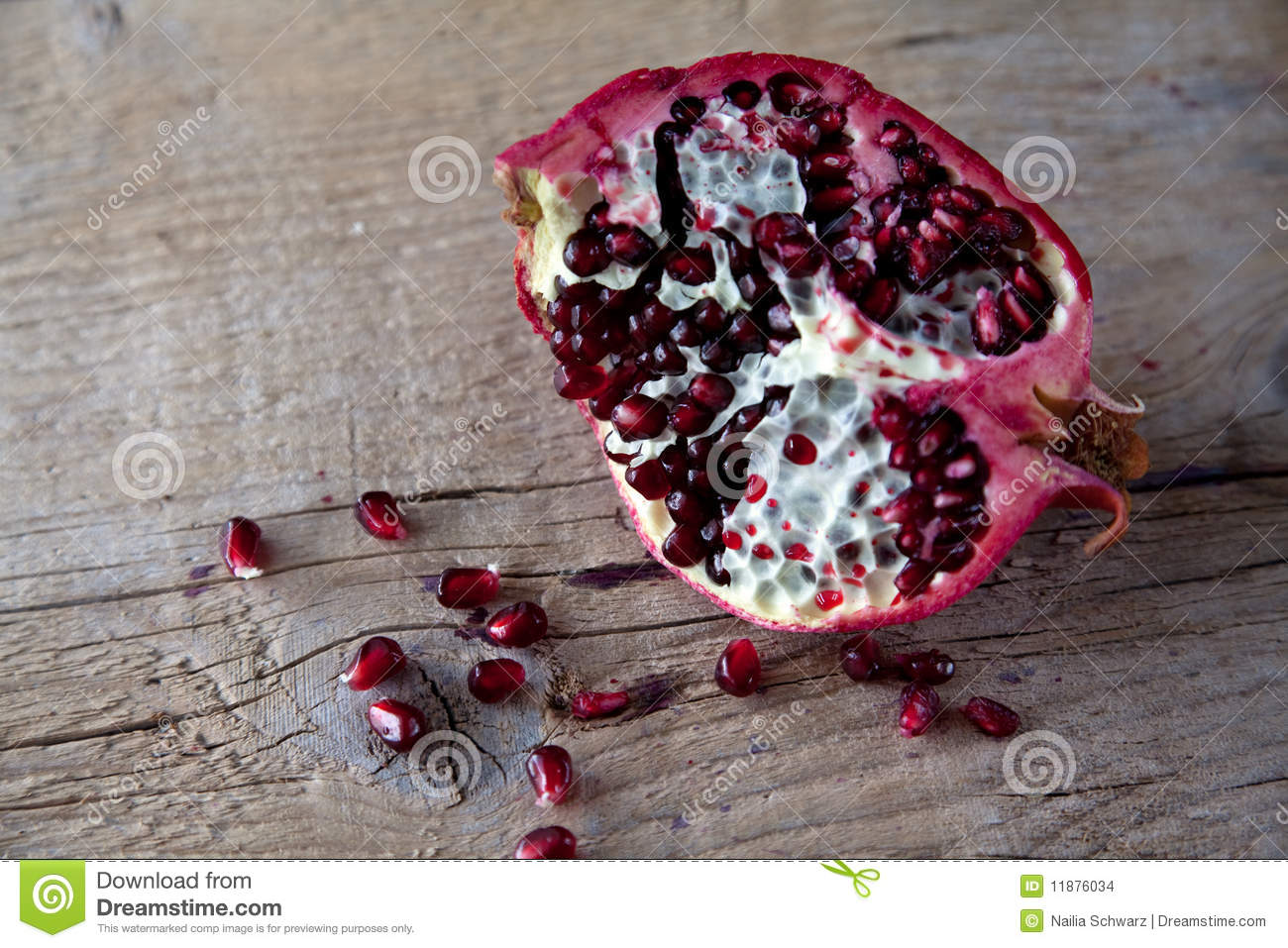 Pomegranate with arils on wooden board