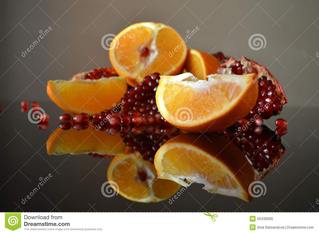 pomegranate-orange-wedges-slices-reflection-surface-table-50430005.jpg