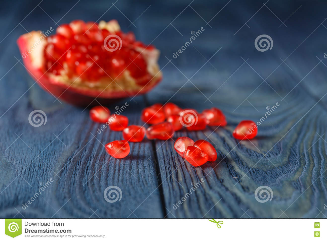 Pomegranate slices and garnet fruit seeds on table. Selective focus