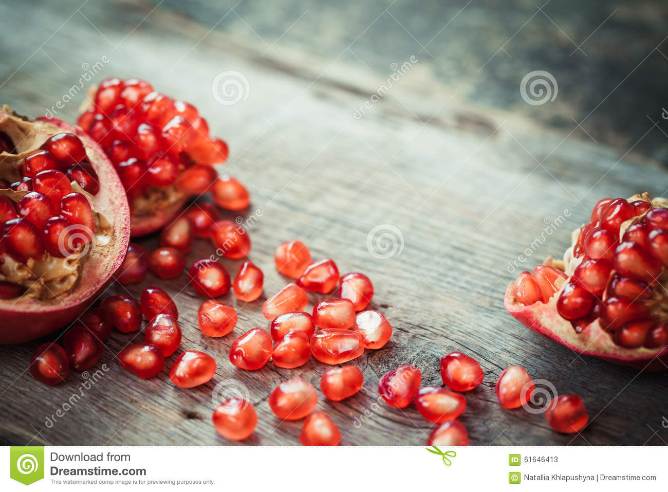 Pomegranate slices and garnet fruit seeds on table.