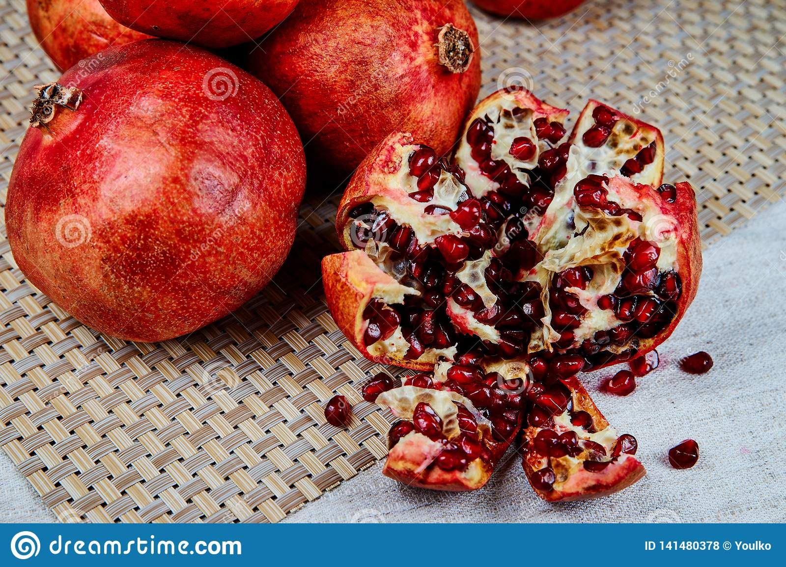 pomegranates on the table on a gray napkin on a linen tablecloth