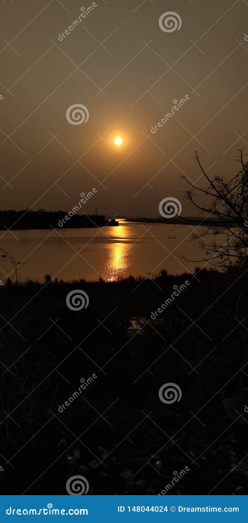 Pomeriggio, accanto al fiume, tramonto, raggi di sole del relfect in acqua