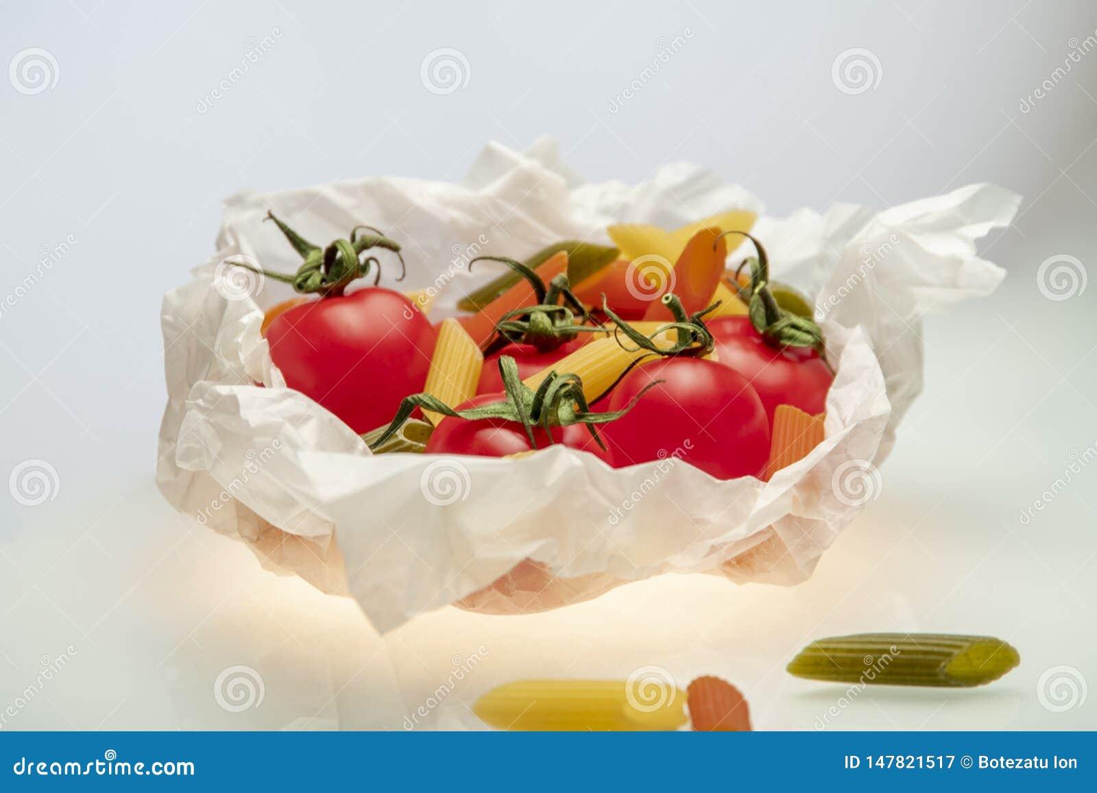 Pomidory i barwiony makaron zawijający w kucharstwie tapetują na czerwonym tle