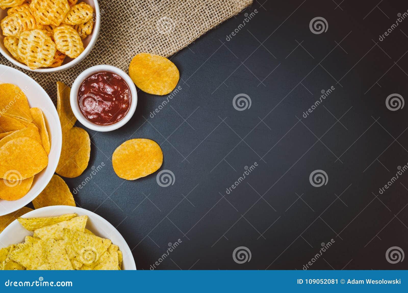 Pommes chips et casse-croûte sur la table noire d ardoise, vue supérieure