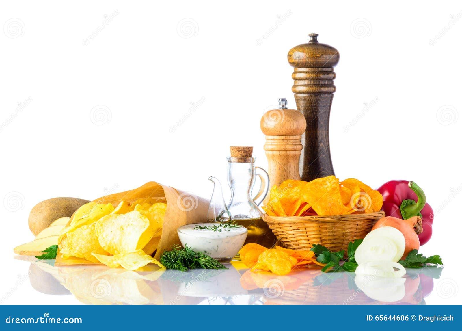 Pommes chips et ingrédients sur le fond blanc