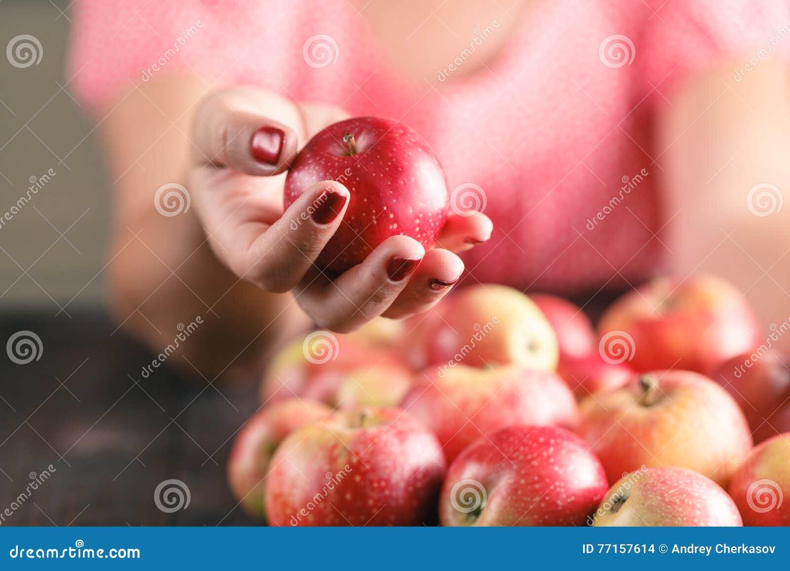 Pommes de prise de femme sur le fond en bois