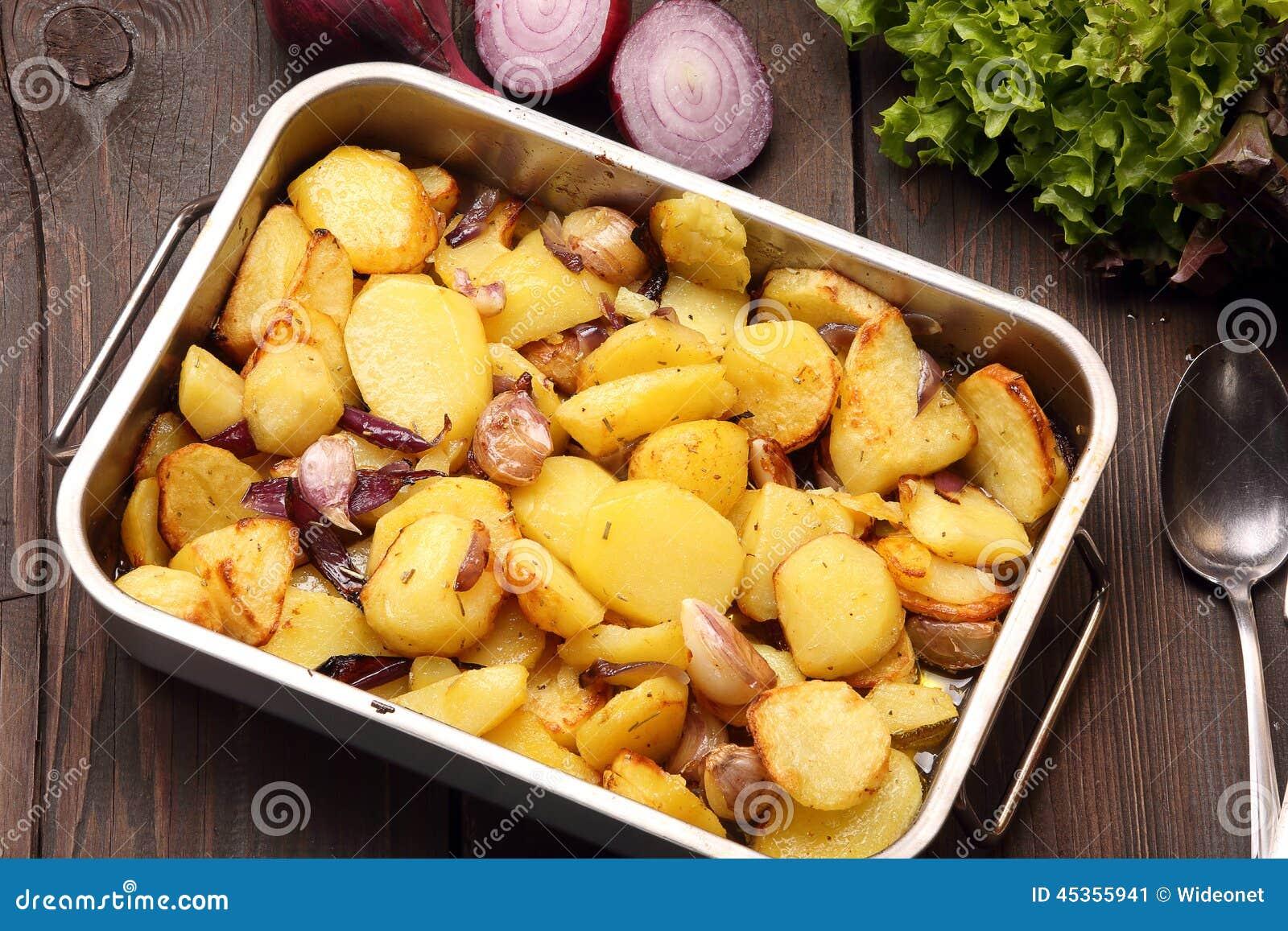 pommes de terre cuites au four dans une casserole de torr faction avec l 39 ail et l 39 oignon photo. Black Bedroom Furniture Sets. Home Design Ideas