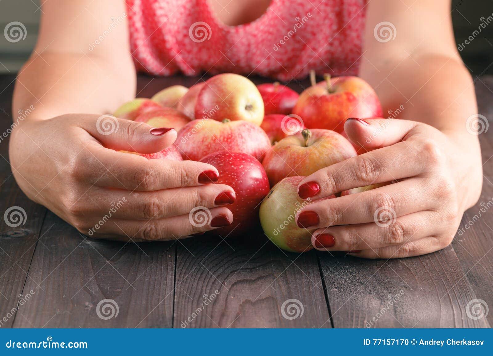 Pommes douces de prise de femme sur le fond en bois