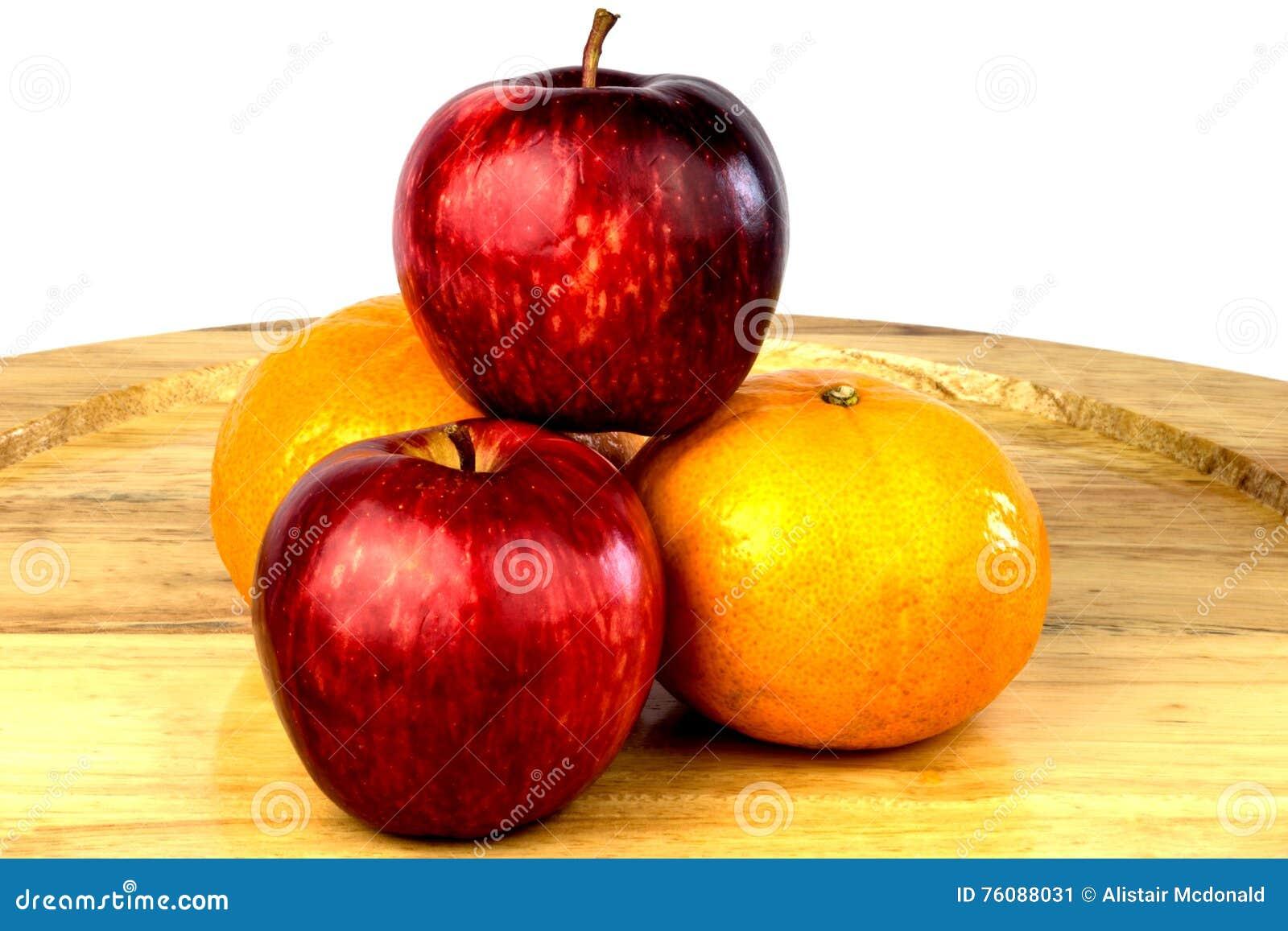 Pommes et oranges sur un plateau en bois