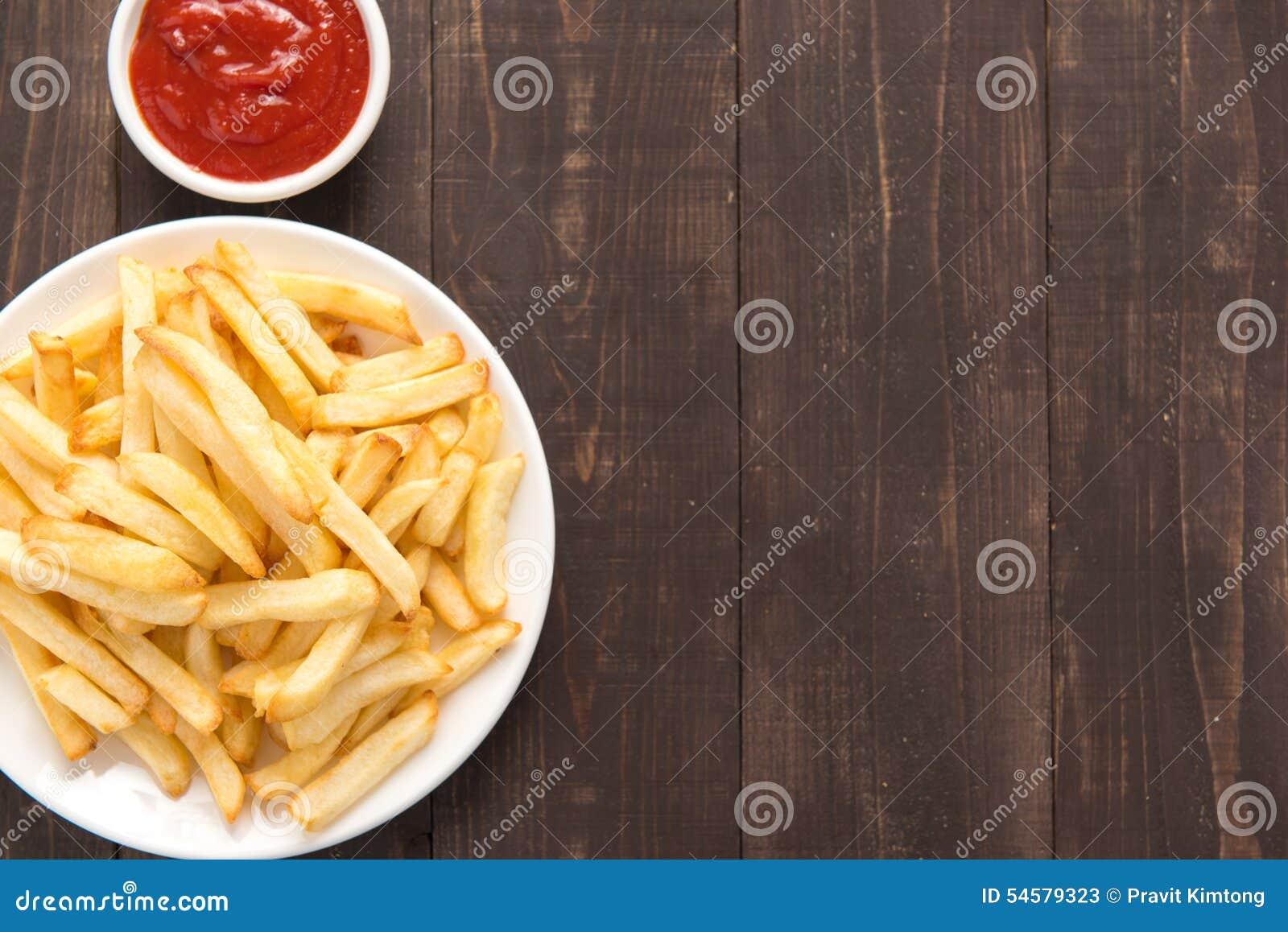 Pommes frites avec le ketchup sur le fond en bois
