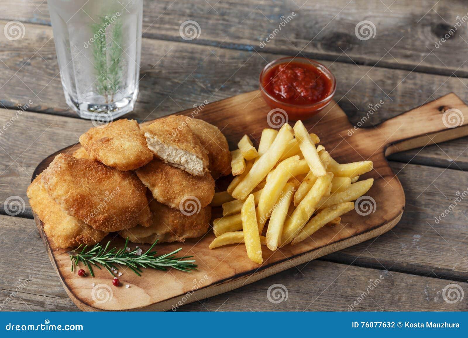 Pommes frites de pépites de poulet sur le conseil avec de la sauce rouge