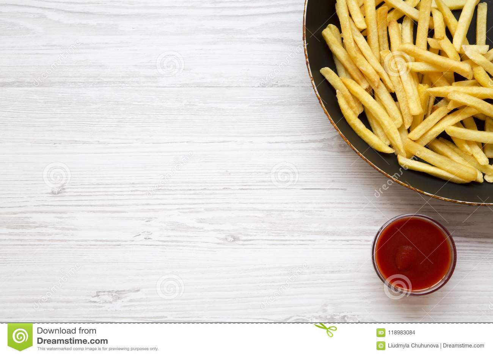 Pommes-Frites in einer Bratpfanne mit Ketschup auf einem weißen Holztisch, Draufsicht