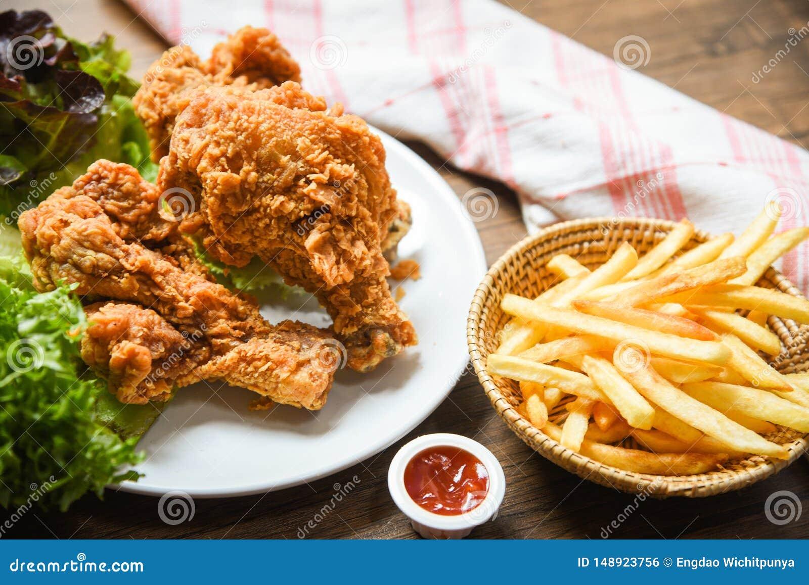 Pommes-Friteskorbketschup auf h?lzernem Speisetischhintergrund und gebratenen dem Huhn knusperig und Salatkopfsalat