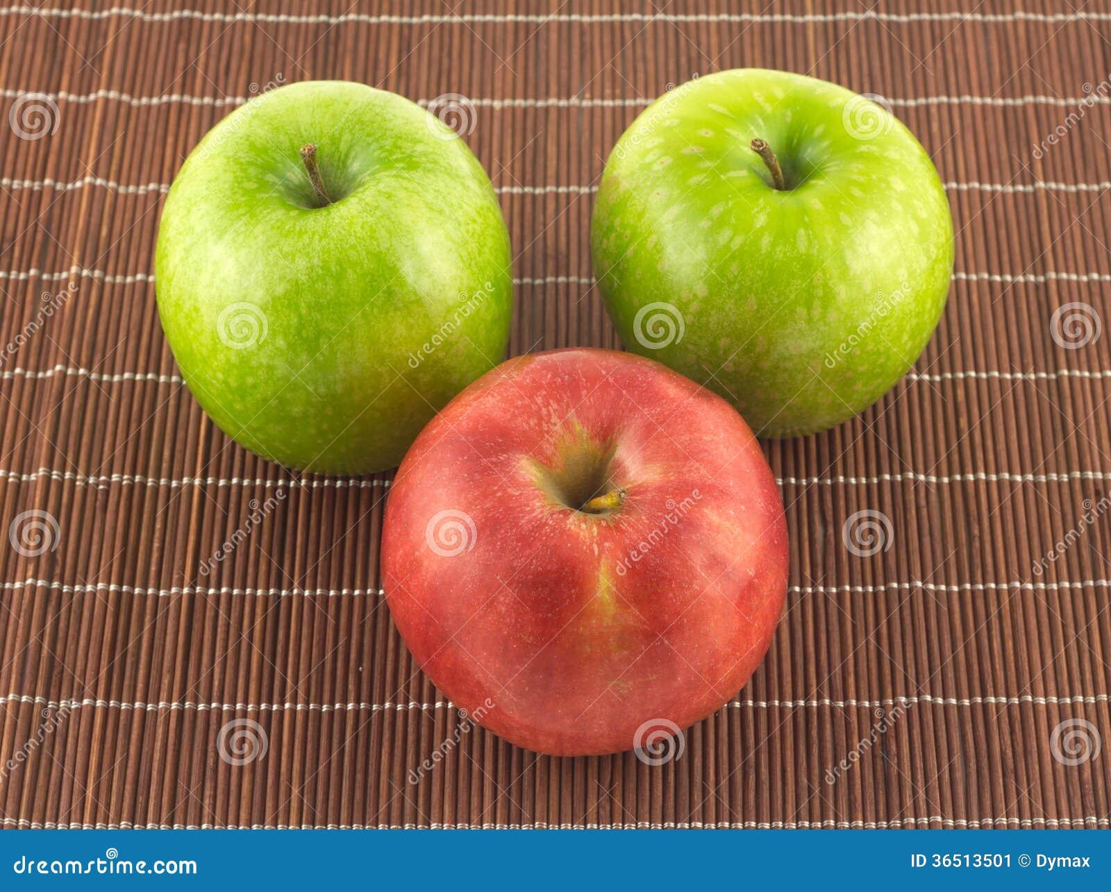 Pommes mûres sur la fin en osier brune de tapis de paille
