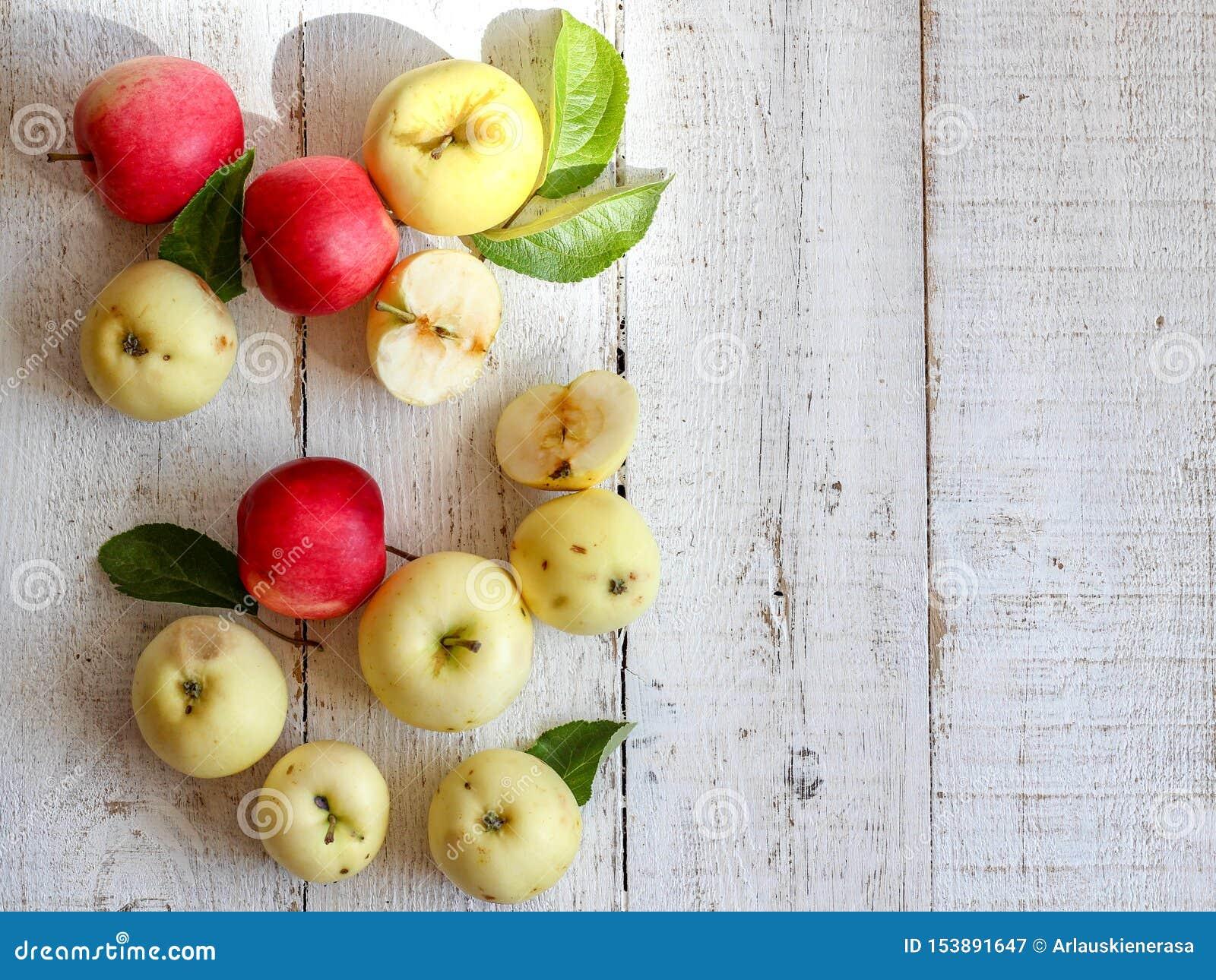 Pommes organiques vertes et rouges sur une table en bois blanche