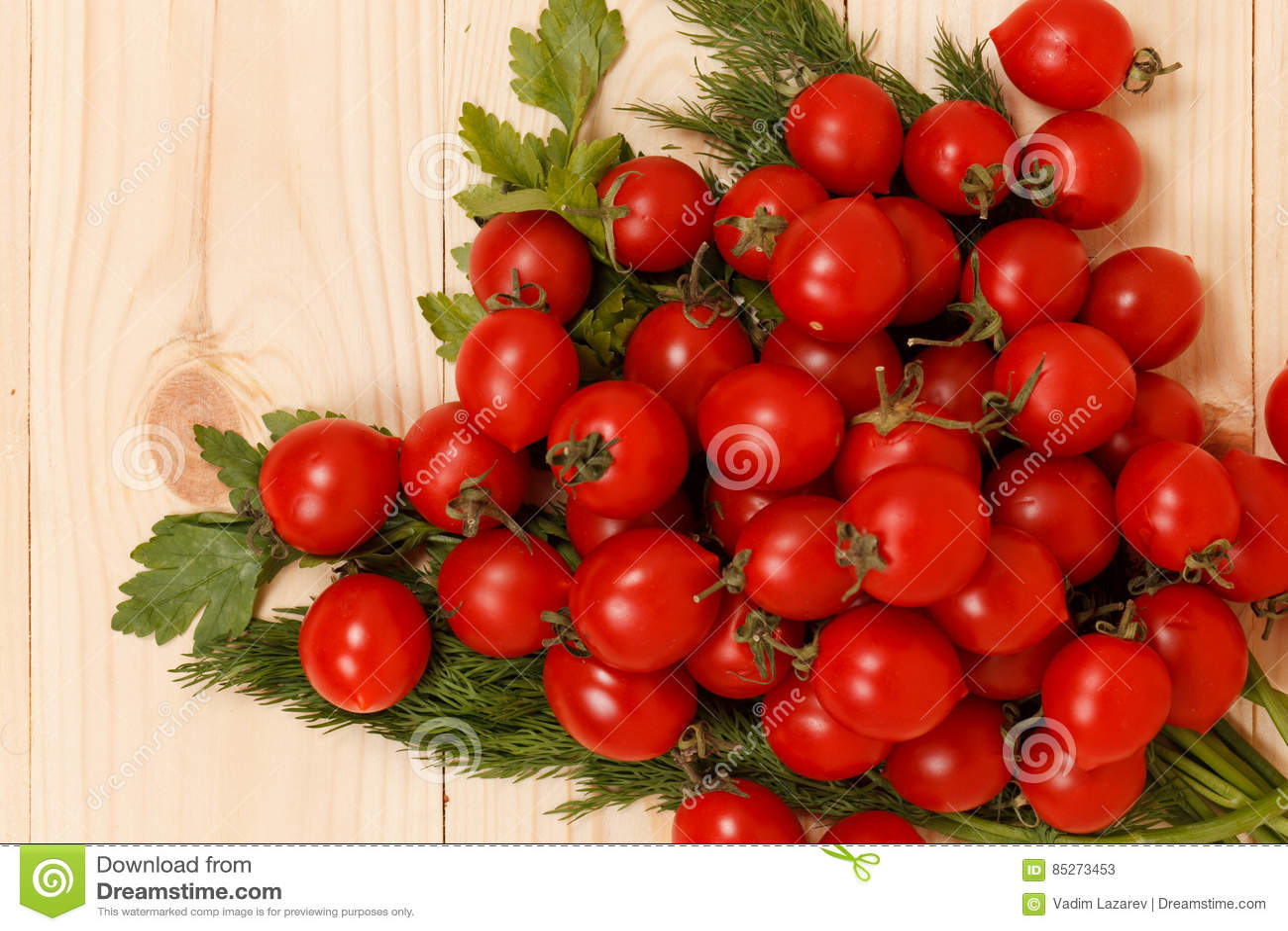 Pomodori ciliegia ed erbe fresche su fondo di legno