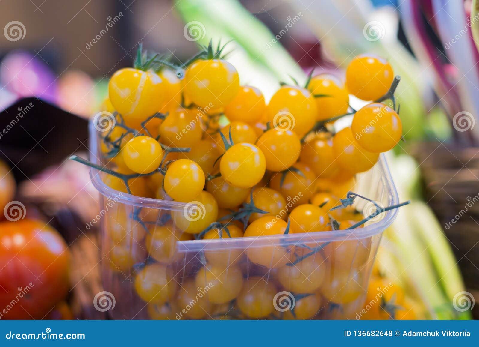 Pomodori ciliegia gialli in recipienti di plastica nel mercato