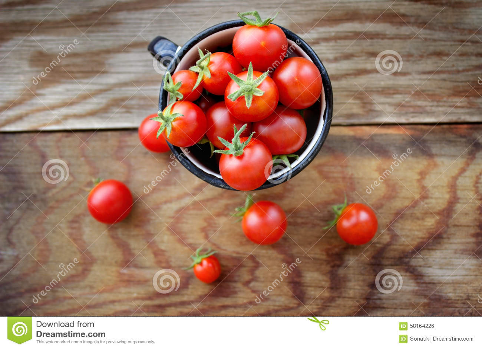 Pomodori ciliegia in tazza su una tavola di legno