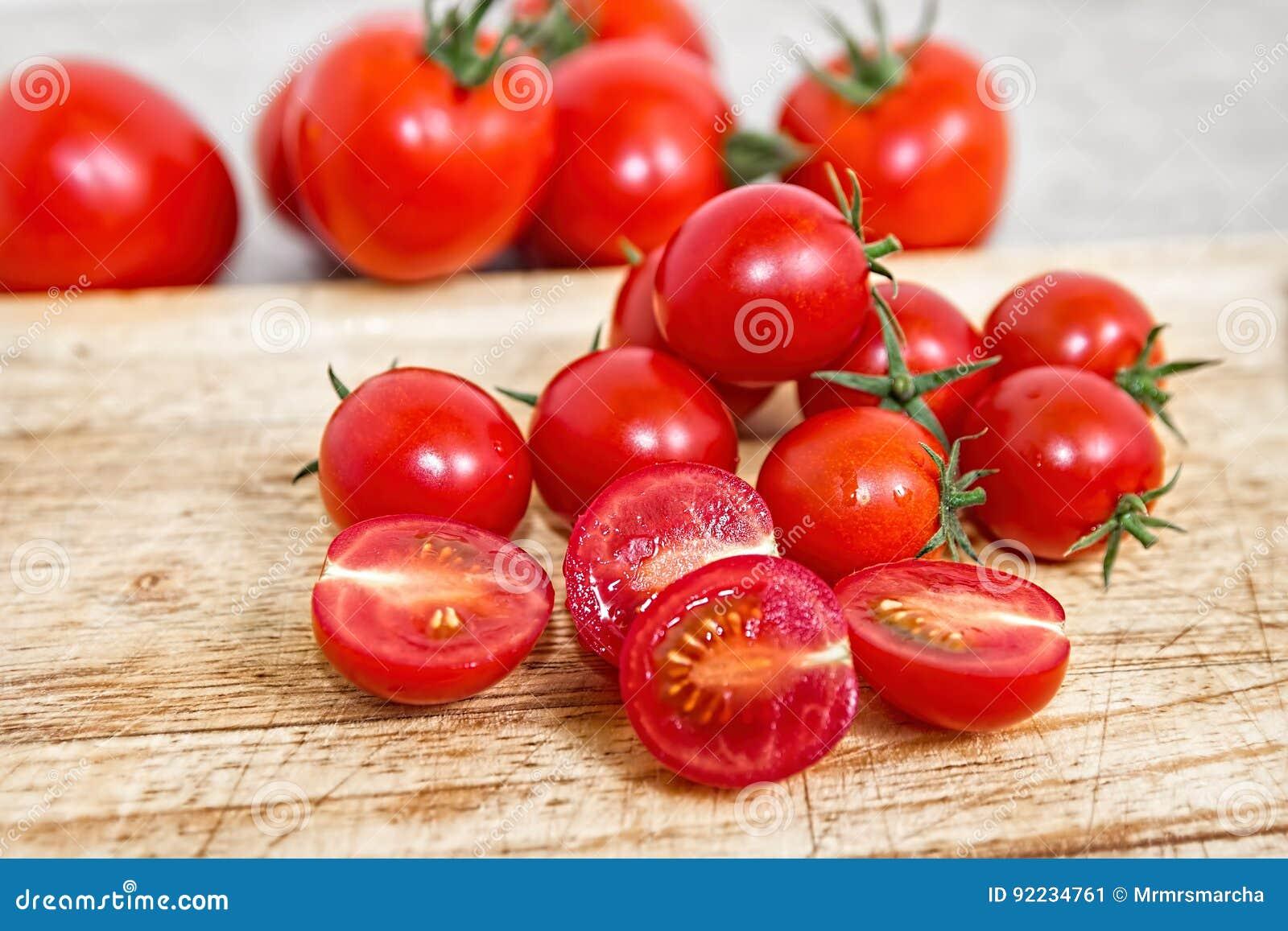 Pomodori di ciliegia su una scheda di taglio di legno Priorità bassa di verdure Bio- prodotti