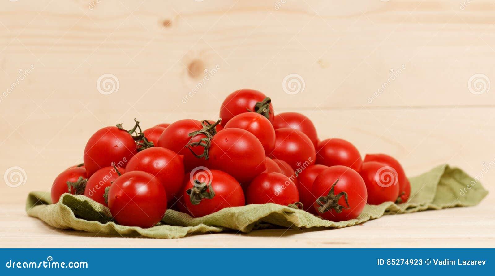 Pomodori sul fondo di legno del tessuto verde