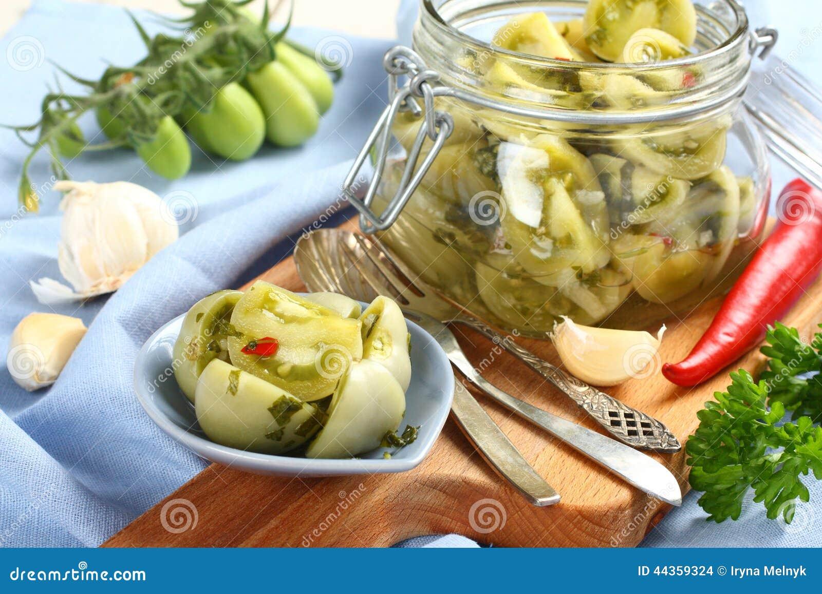 Pomodori verdi marinati in ciotola blu ed in barattolo di vetro