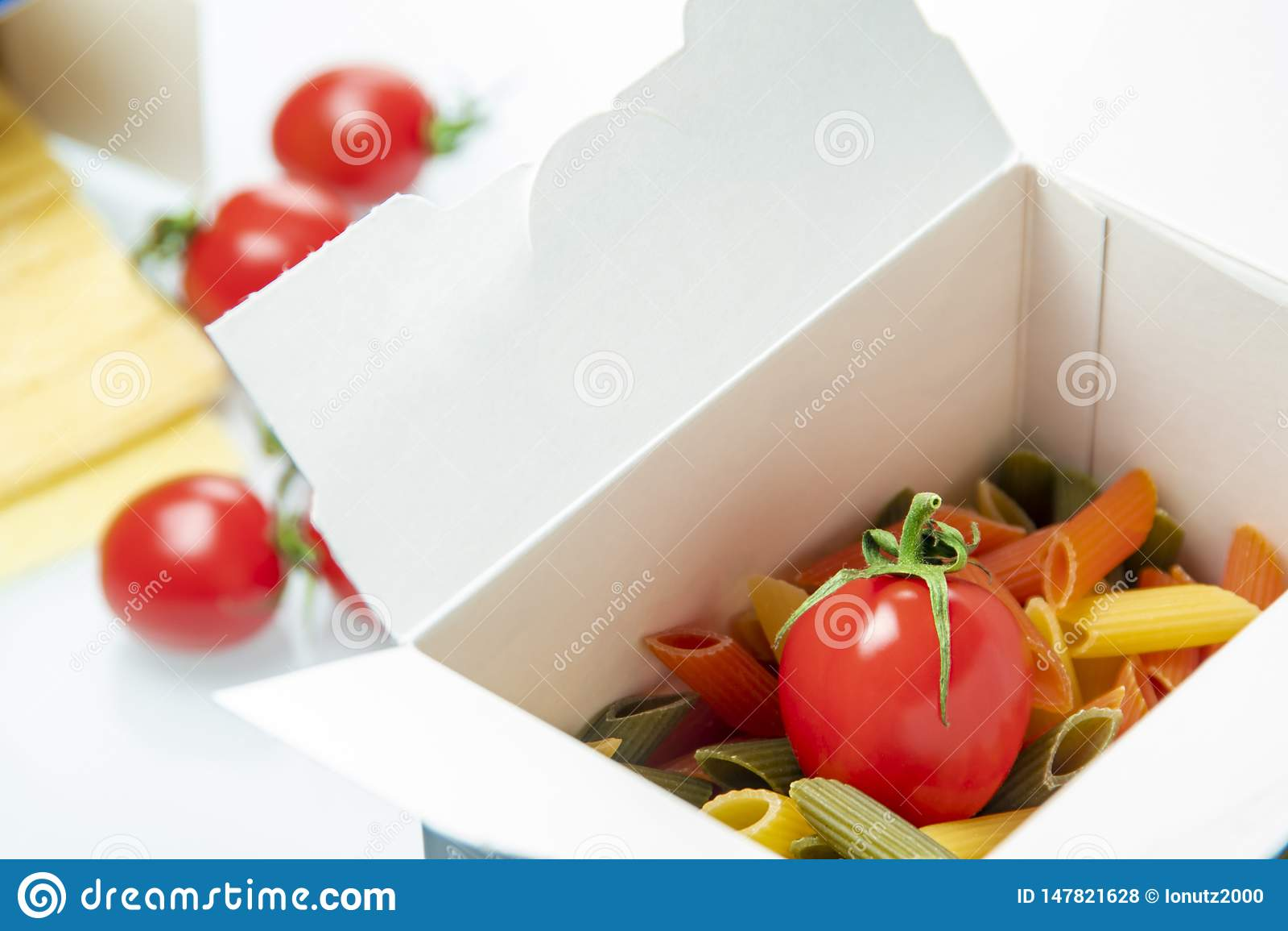 Pomodoro disposto in un contenitore di pasta di colore