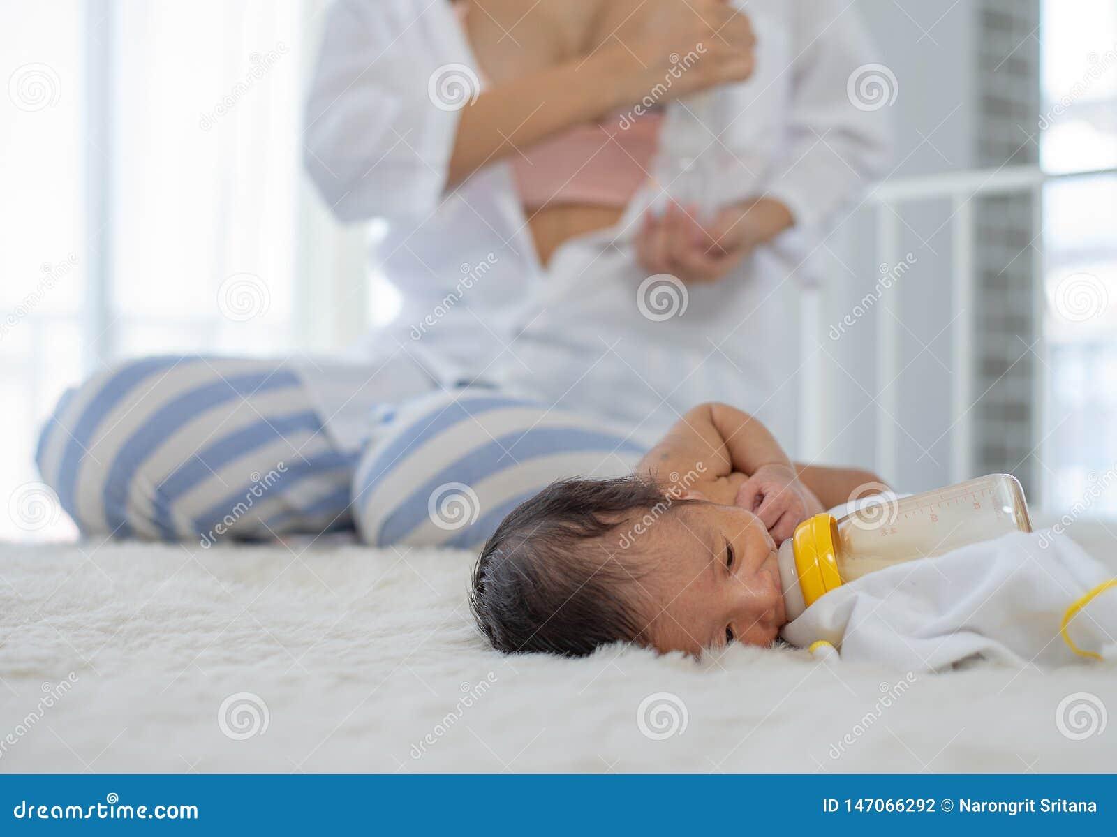 Pompa bianca del latte materno di uso della madre della camicia per ottenere latte materno e seduta vicino al sonno neonato sul l