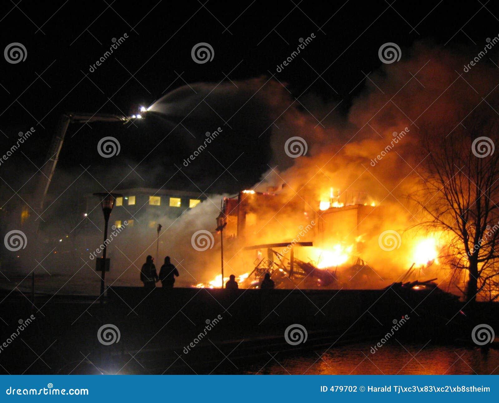 Pompieri che mettono casa fuori bruciante.