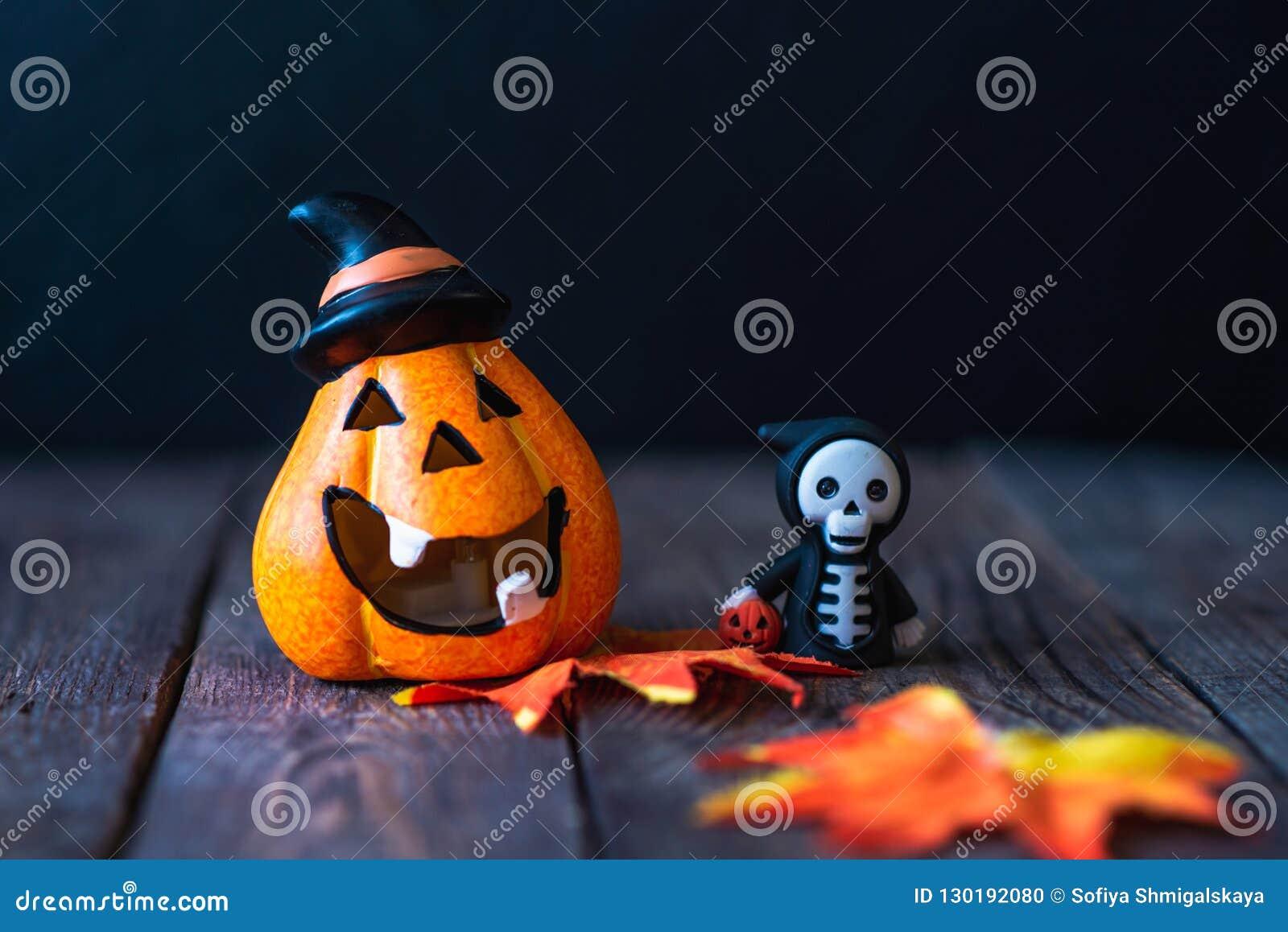 Pompoen met een gezicht en een skelet in een hoodie
