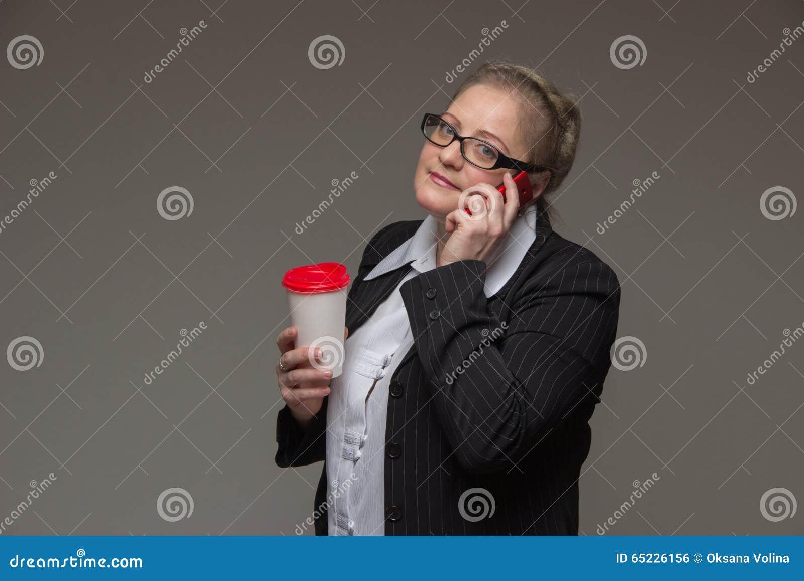 Pomyślna biznesowa kobieta no jest młoda w kostiumu z kawowy tal