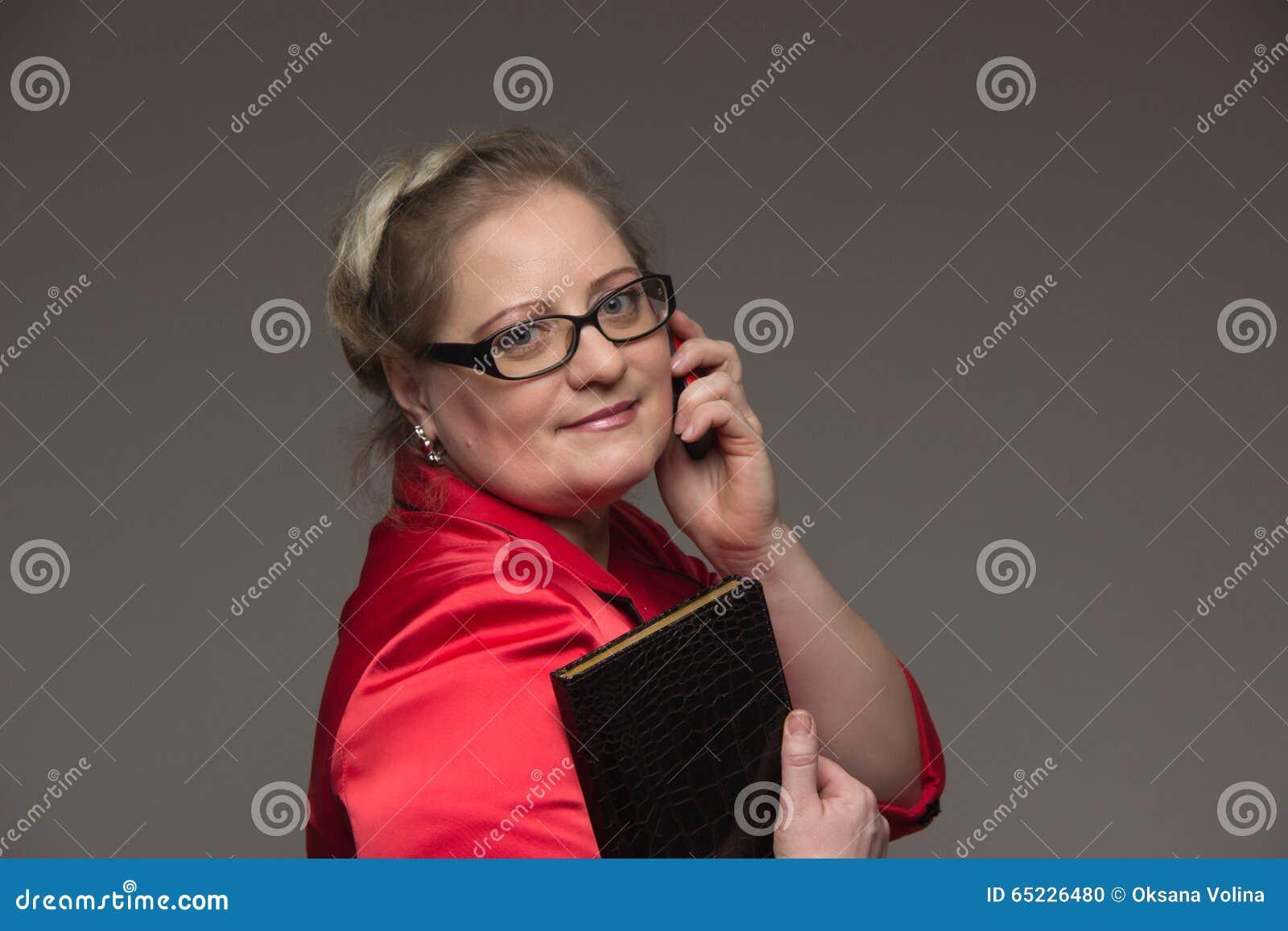 Pomyślna biznesowa kobieta no jest młoda w kostiumu z notatnikiem