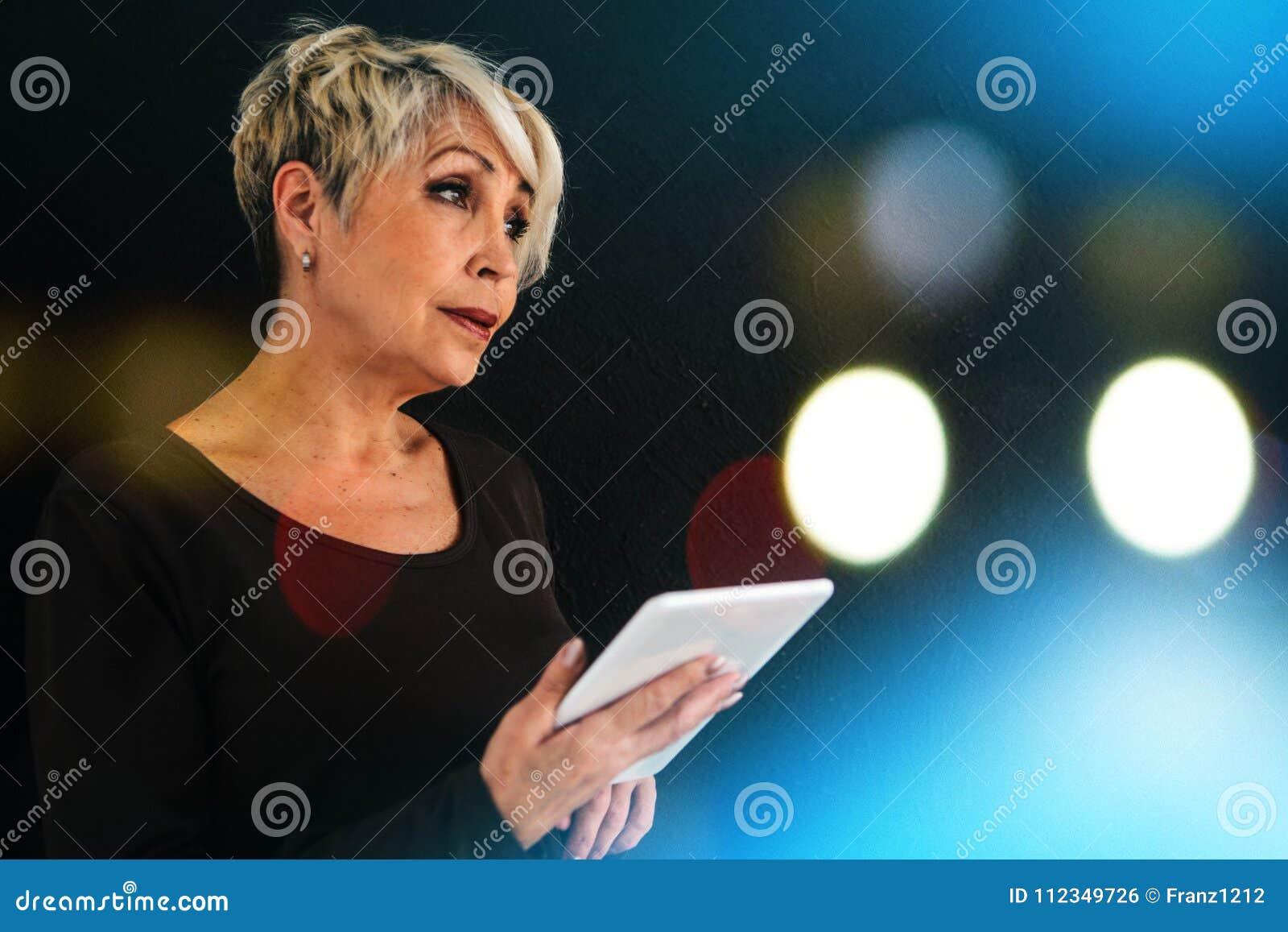 Pomyślna pozytywna nowożytna starsza kobieta trzyma pastylkę w ona i używa je ręki Nowożytny i