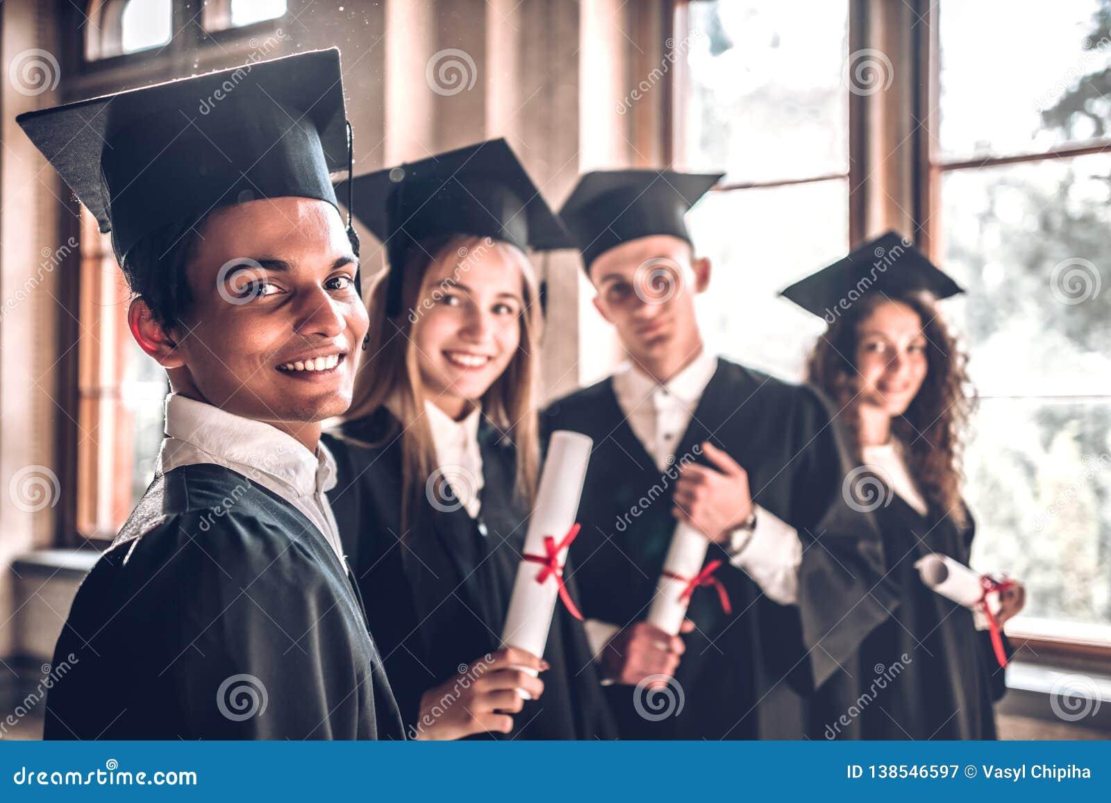 Pomyślne kariery - tutaj przychodzimy! Grupa uśmiechnięci szkoła wyższa absolwenci stoi wpólnie w uniwersyteckiej i ono uśmiecha