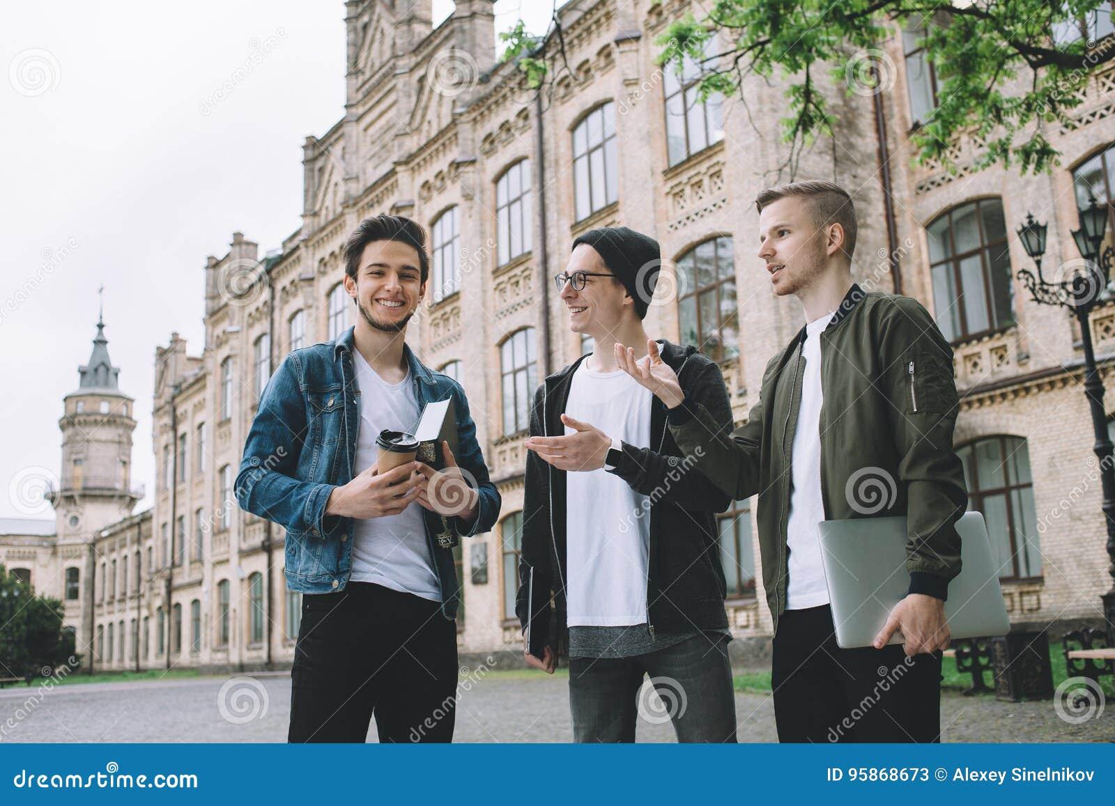 Pomyślni szczęśliwi ucznie stoi blisko kampusu lub uniwersyteta outside