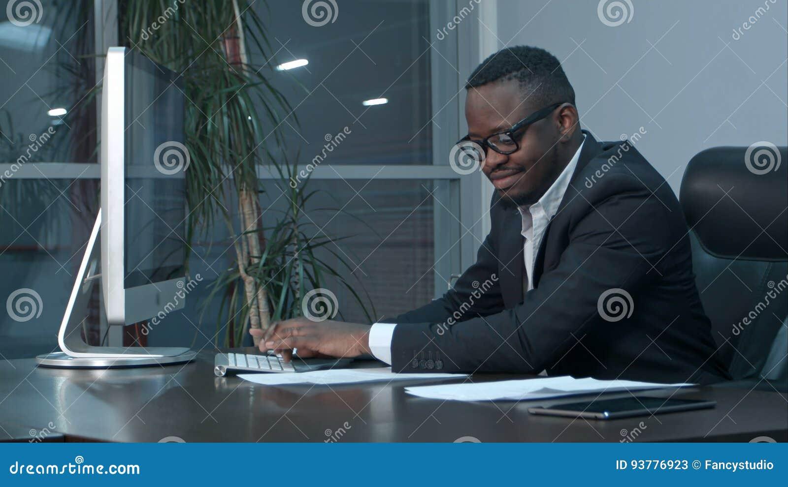 Pomyślny amerykanina afrykańskiego pochodzenia biznesmena obsiadanie przy biurkiem, pracujący na rodzajowym laptopie, pisać na ma
