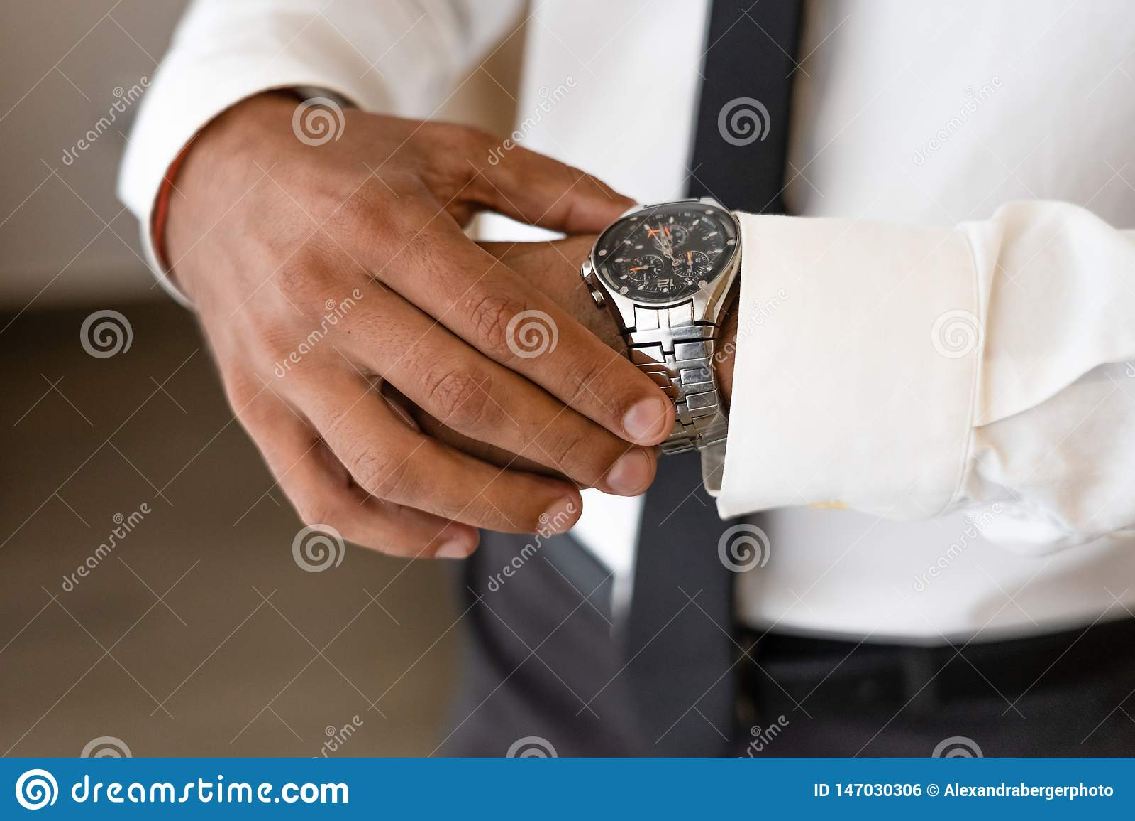 Pomyślny mężczyzna z białymi koszula i krawata spojrzeniami na zegarku