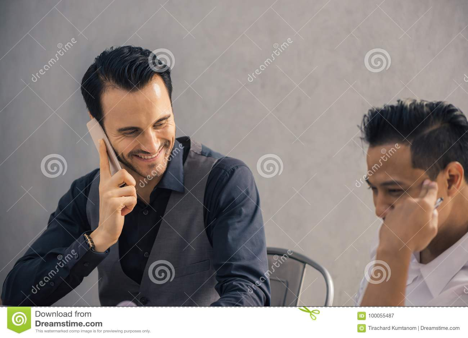 Pomyślny projekt Dwa rozochoconego ludzie biznesu dyskutuje coś i ono uśmiecha się w formalwear podczas gdy jeden one wskazywać c