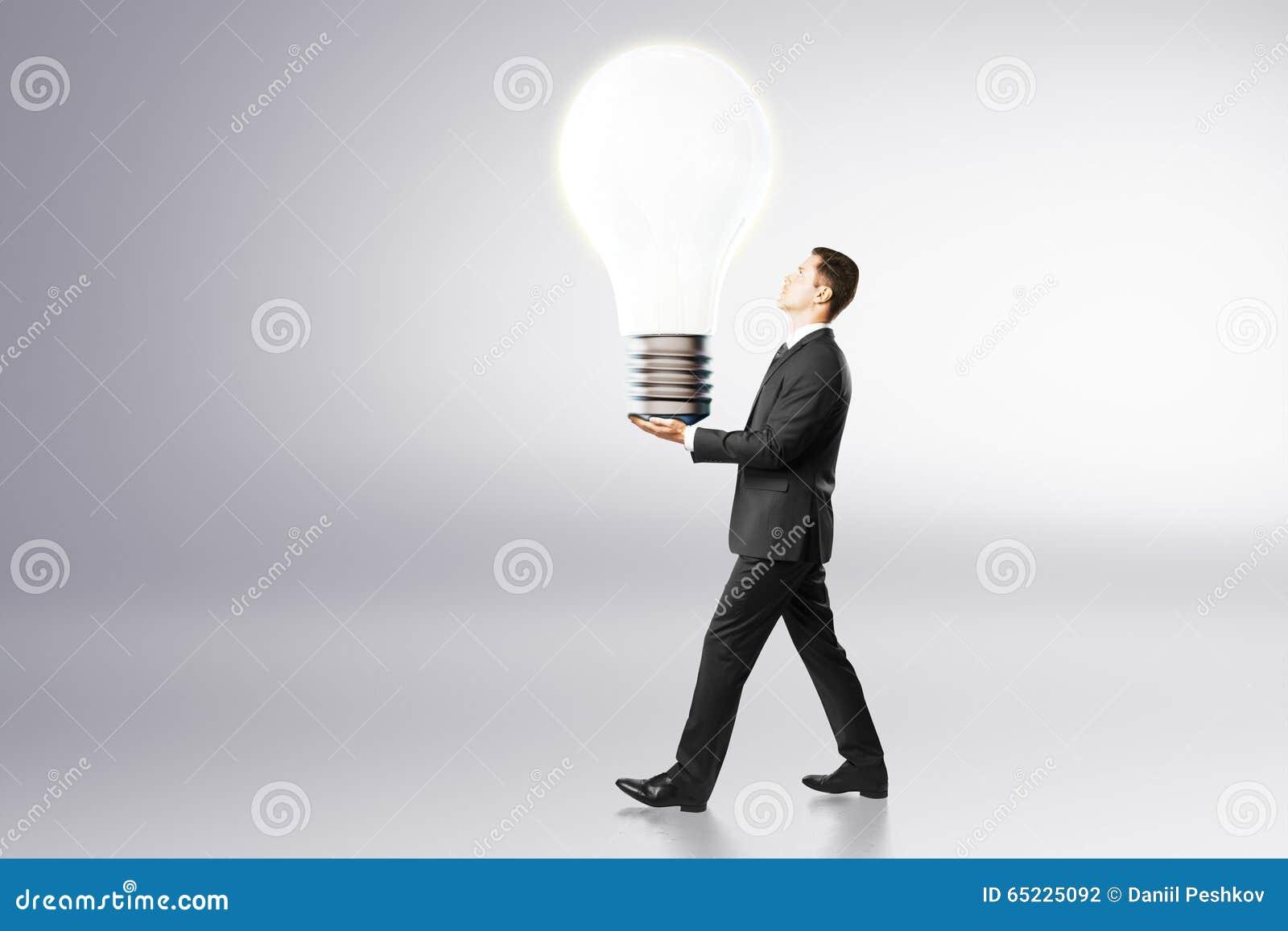 Pomysłu pojęcie z biznesmenem niesie dużą żarówkę