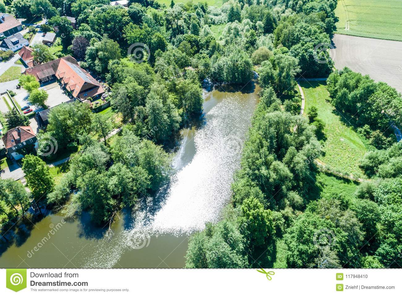 The pond at the moated castle Neuhaus from the air, with bushes and trees, at the edge of the village