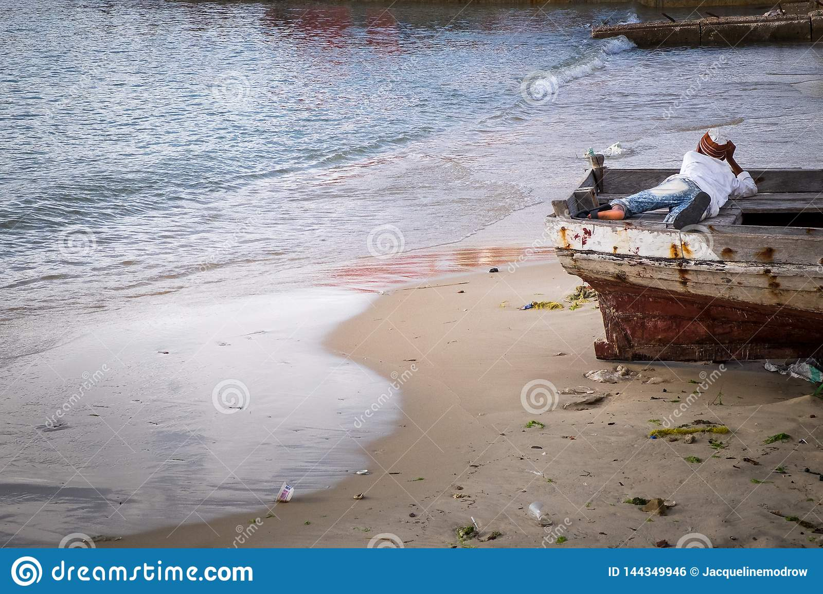 A young boy laying in a boat appearing to be in deep thought