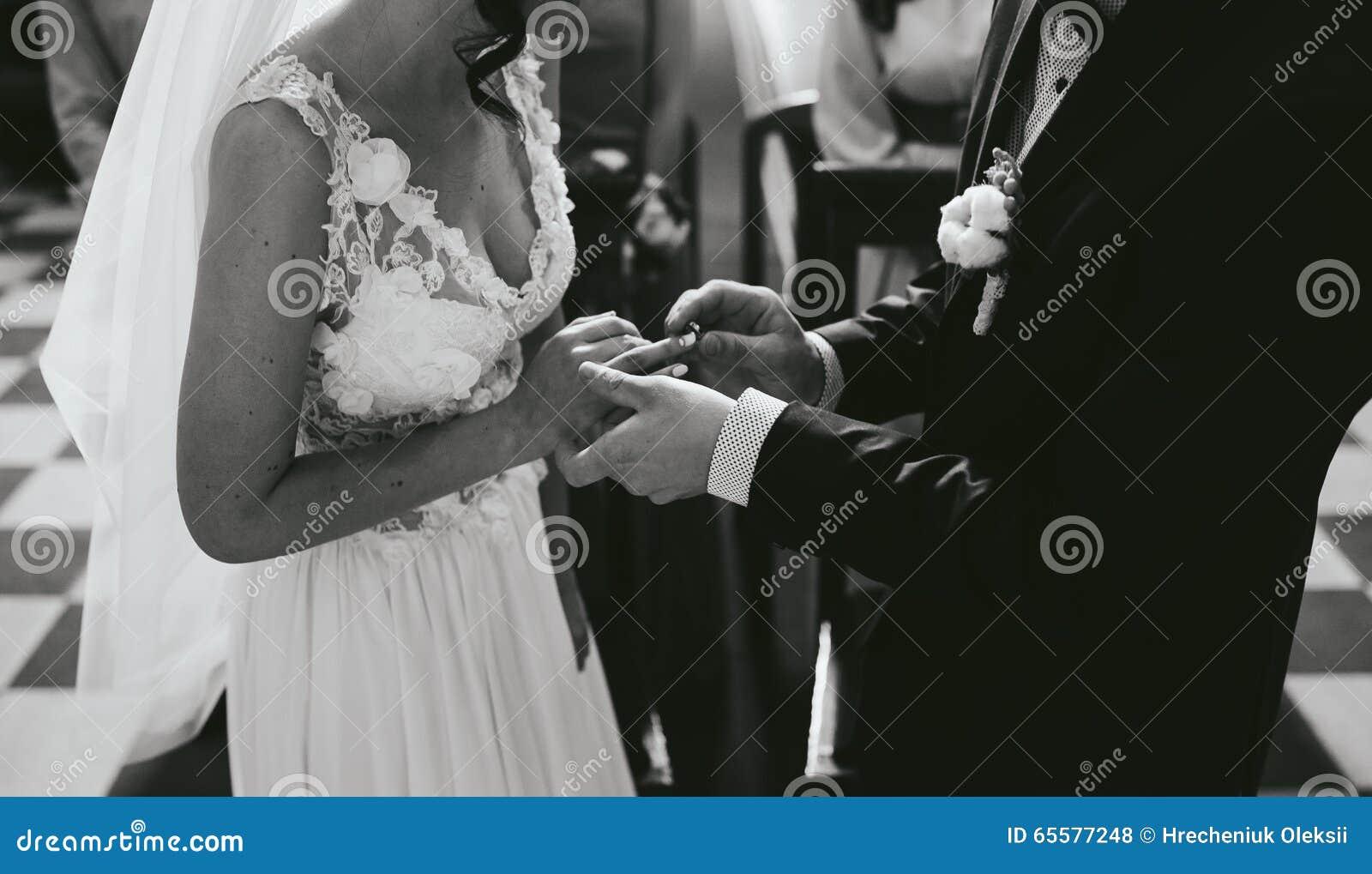 Pondo a aliança de casamento sobre