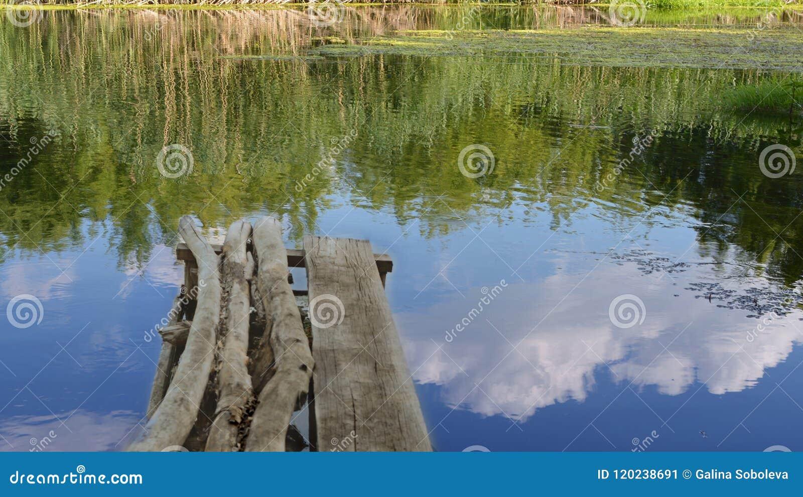 Pont de CkgroundA de vieux faisceaux au-dessus de la rivière, d une réflexion du ciel bleu et des nuages