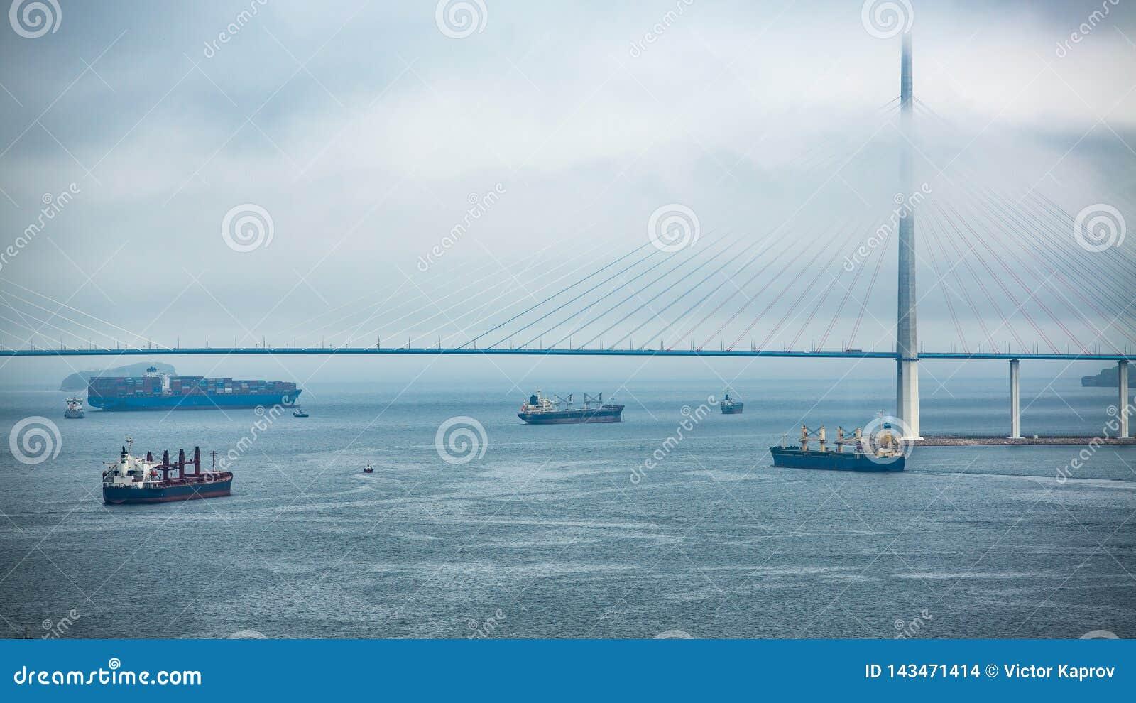 Pont et bateaux dans le brouillard par temps nuageux