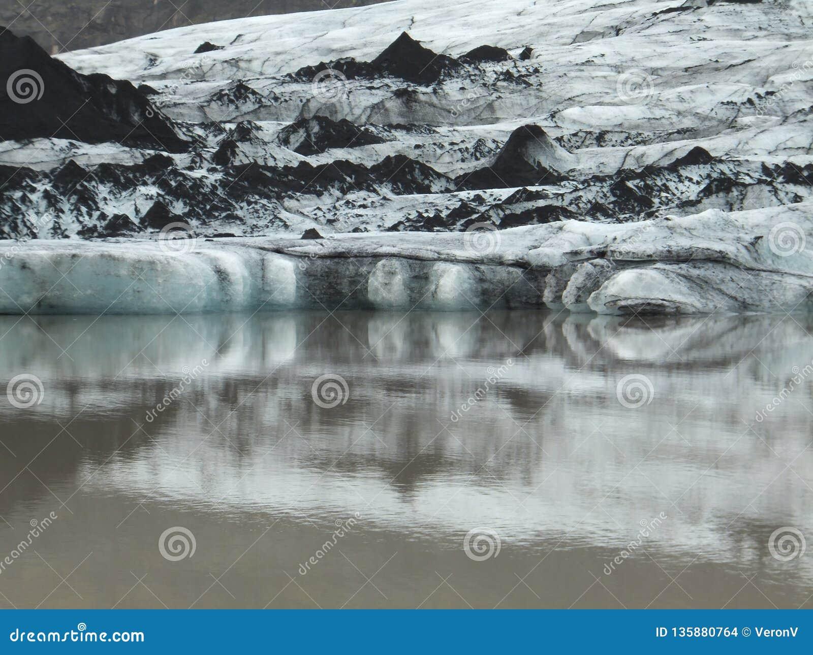 Ponta da geleira do lheimajökull do ³ de Sà no sul de Islândia, com camadas alternas do gelo branco e luz-azul e de solo preto