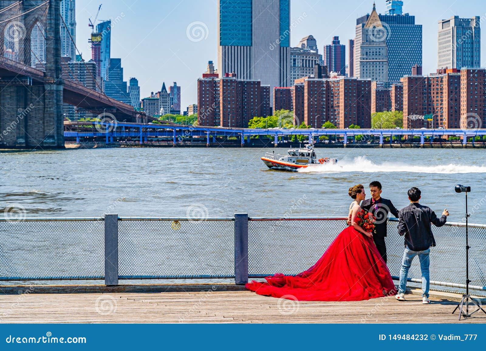 Ponte de Brooklyn com mais baixa skyline de Manhattan, sessão da forma com um vestido vermelho enorme em New York City