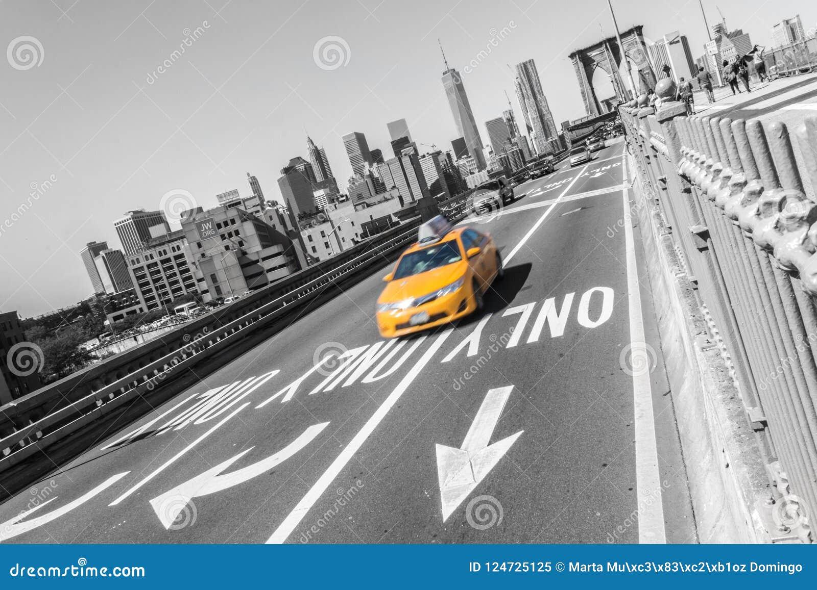 Ponte de Brooklyn com o carro rápido amarelo do táxi em New York City NYC