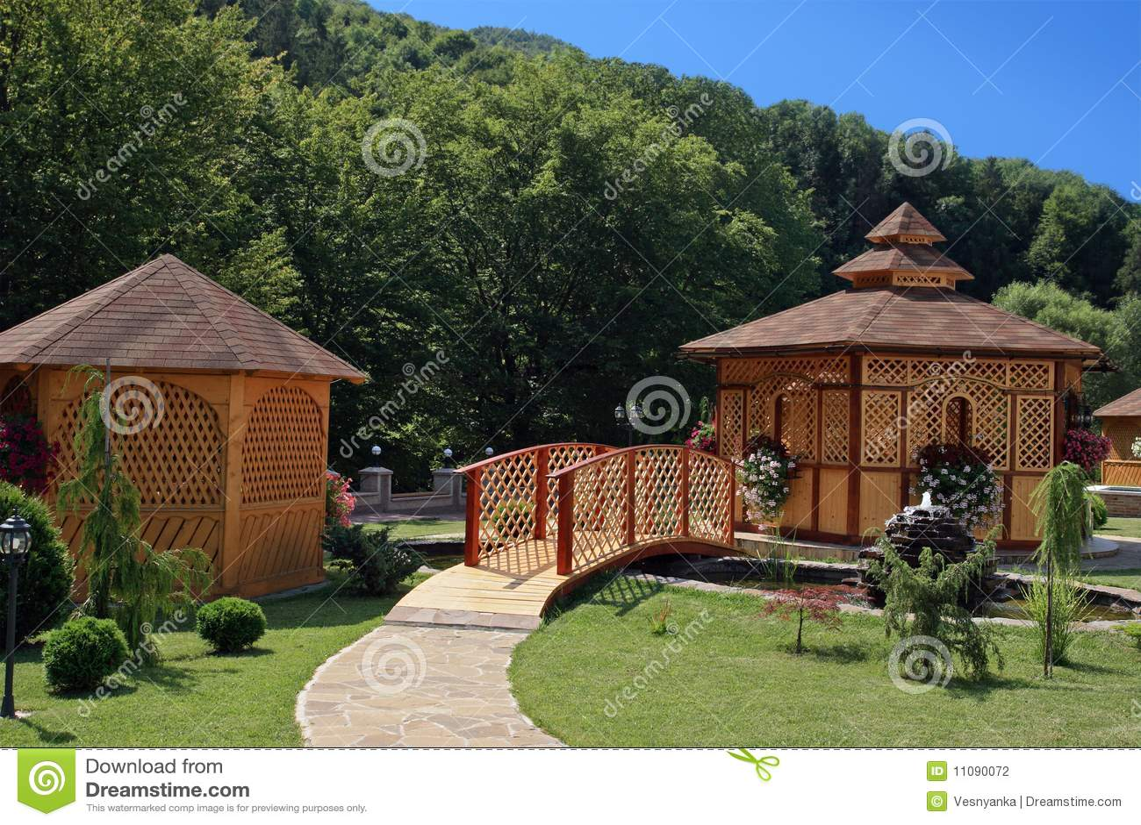 gazebo jardim madeira:Um summerhouse em um jardim doméstico no verão, com a ponte pequena