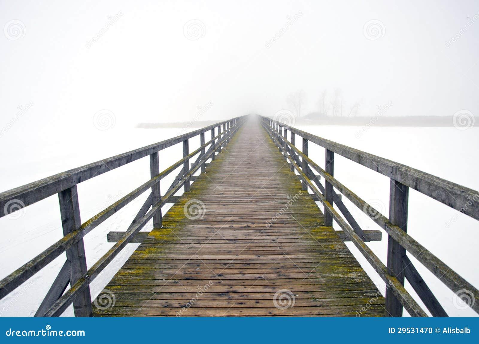 Ponte de madeira velha na névoa da manhã do inverno